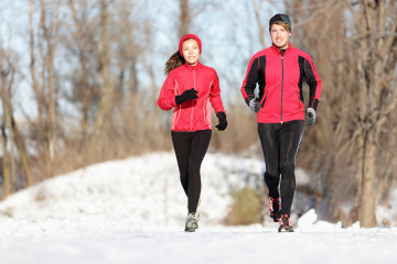 Sport couple running in winter. Runners jogging in snow in city