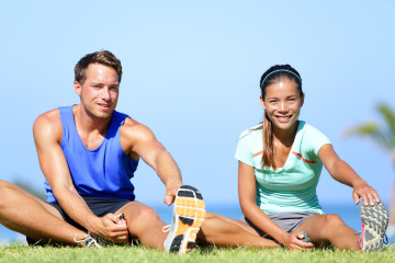 Stretching exercises - Fitness couple outside doing stretches ex