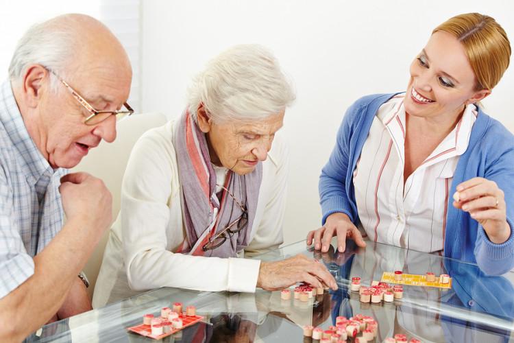 Senior couple playing Bingo with eldercare assistant in nursing