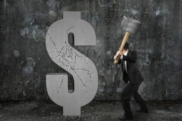 Businessman Holding Hammer Hitting Cracked Dollar Sign With Mott