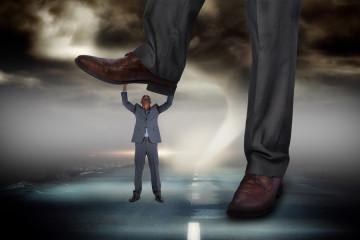 Composite image of businessman stepping on tiny businessman agai