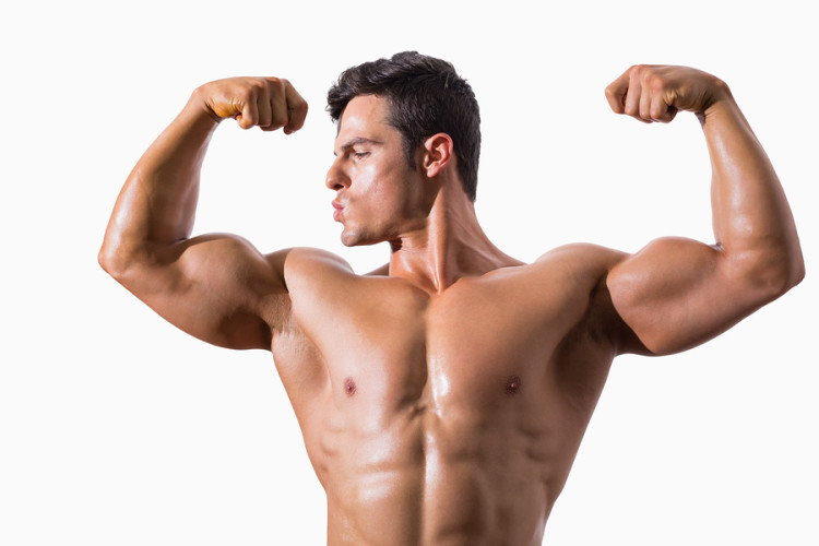 Portrait of a muscular young man flexing muscles over white back