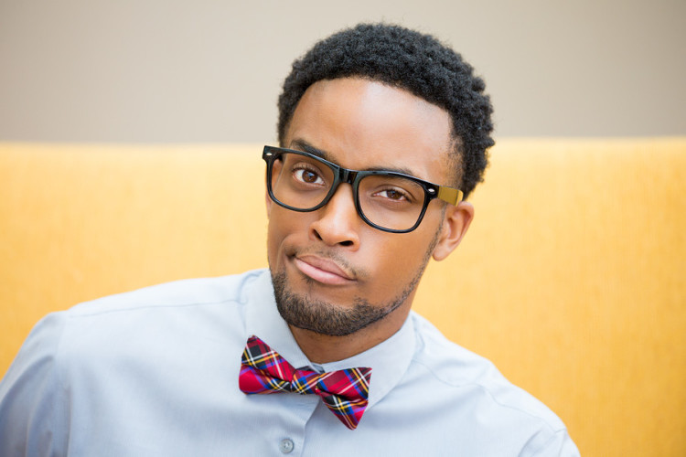 Closeup portrait of handsome cocky guy with big black glasses and blue shirt looking at you camera gesture skeptically. Negative human emotion facial expression feeling