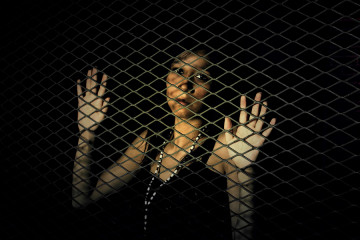 Woman behind a metal fence