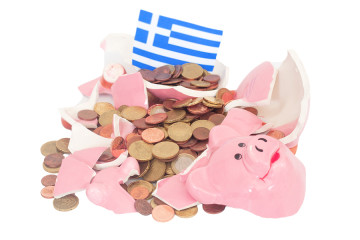 Broken Piggy bank with lot of change money. In the background is a greek flag.Methaphor for the financial crisis in greece. Isolated on white.