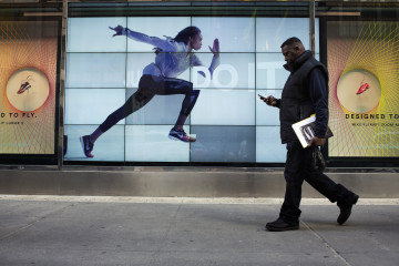 A pedestrian checks a mobile device as he walks past the window display of a Nike Inc. Niketown store in New York, U.S., on Wednesday, March 18, 2015. Nike is scheduled to release a third-quarter earnings report following the close of U.S. financial markets on March 19. Photographer: Victor J. Blue/Bloomberg
