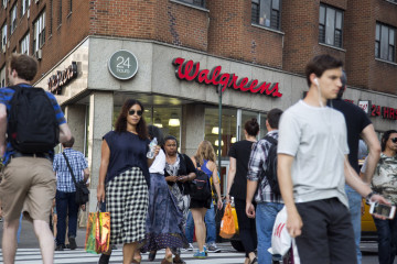 Pedestrians walk past a Walgreens Boots Alliance Inc. store in New York, U.S., on Wednesday, June 10, 2015. Walgreens is redoing its stores with what's meant to be a more appealing cosmetics area with a wider array of products, even as it scales back its fresh food offering. Most prominent will be the company's own Boots No7 skincare line, which has proved successful at drawing customers to stores in Europe. Photographer: Michael Nagle/Bloomberg