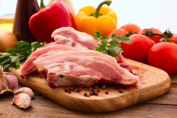 Sliced pieces of raw Meat for barbecue with fresh Vegetables and Mushrooms on wooden surface. Meat Raw Steak. Beef Steak BBQ. Tomatoes, peppers, spices for cooking meat.