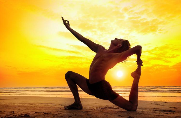 Man doing Yoga on the beach near the ocean in India