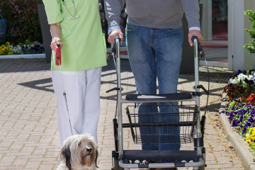 Smiling Blond Nurse Holding onto Arm of Senior Man Helping Man with Walker Walk Dog on Leash Outdoors in front of Retirement Building on Sunny Day