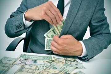 bigstock-man-in-suit-sitting-in-a-desk-668993321