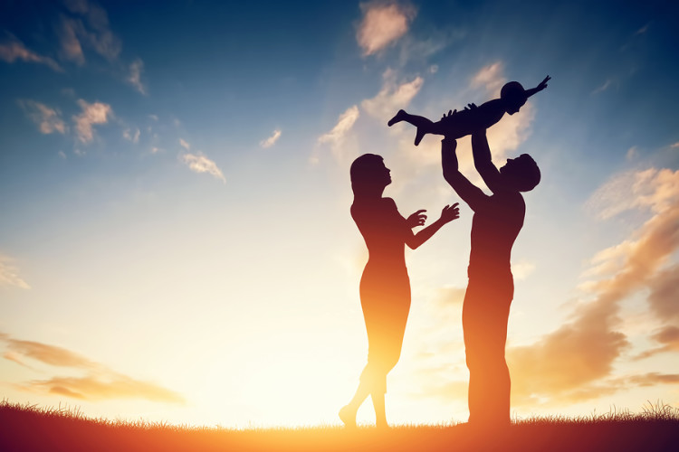 Happy family together, parents with their little child at sunset