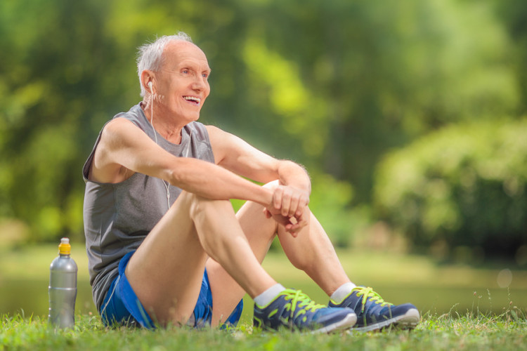 Athletic senior in sportswear sitting on grass in a park and listening to music on headphones