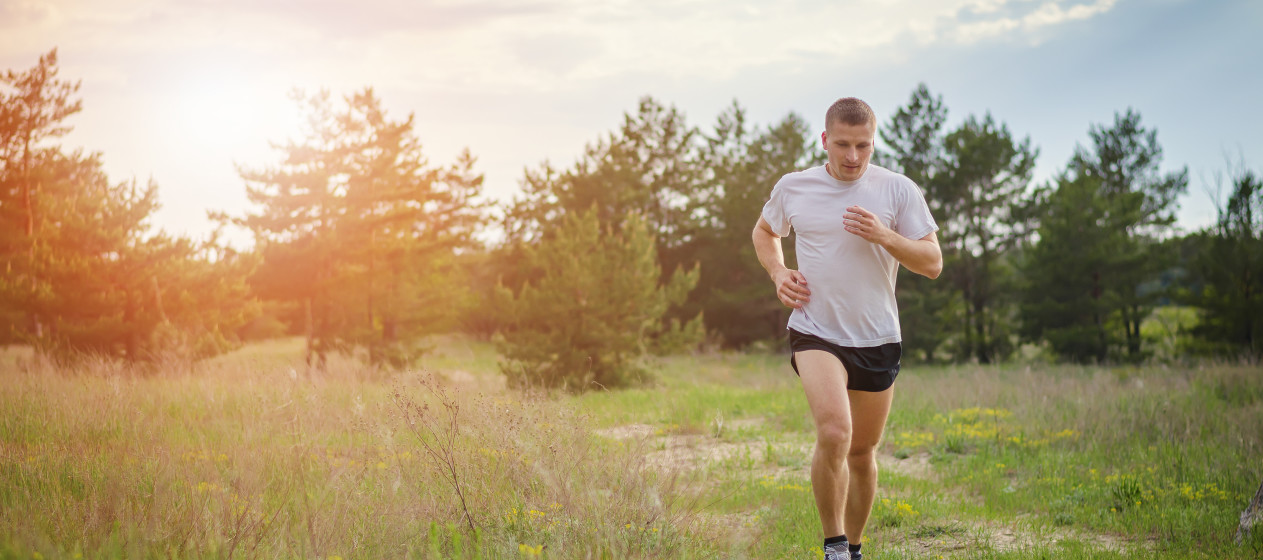 Young athletic man running outdoors in a field on a background sunset. The sun's rays illuminate the man