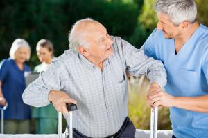 Male and female nurses helping senior people in nursing home