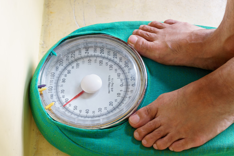 Man's feet standing on weighing machine weighing scale