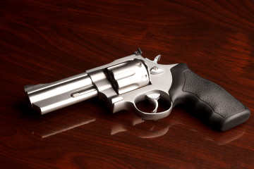 Clean .357 revolver laying on reflective wooden table