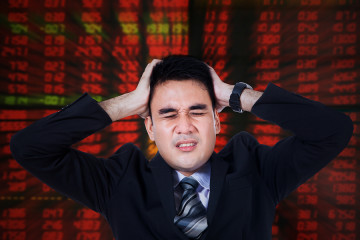 Photo of male broker looks stressful with hands on head and red stock background