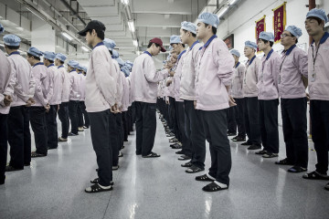 Workers line up for role call before entering their work stations at a Pegatron factory in Shanghai, China. Photographer: Qilai Shen/Bloomberg