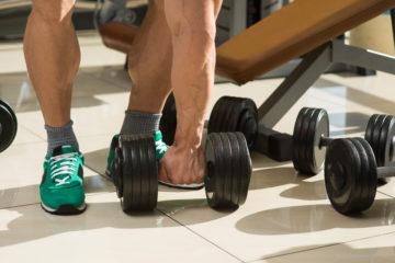 Bodybuilder picks up dumbbells. A few dumbbells on the floor. Muscular man's hand taking dumbbell.