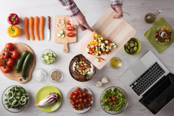Man's hands cooking at home and chopping fresh vegetables on a cutting board kitchen tools and food ingredients all around top view