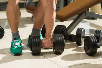 Bodybuilder picks up dumbbells. A few dumbbells on the floor. Muscular man's hand taking dumbbell.
