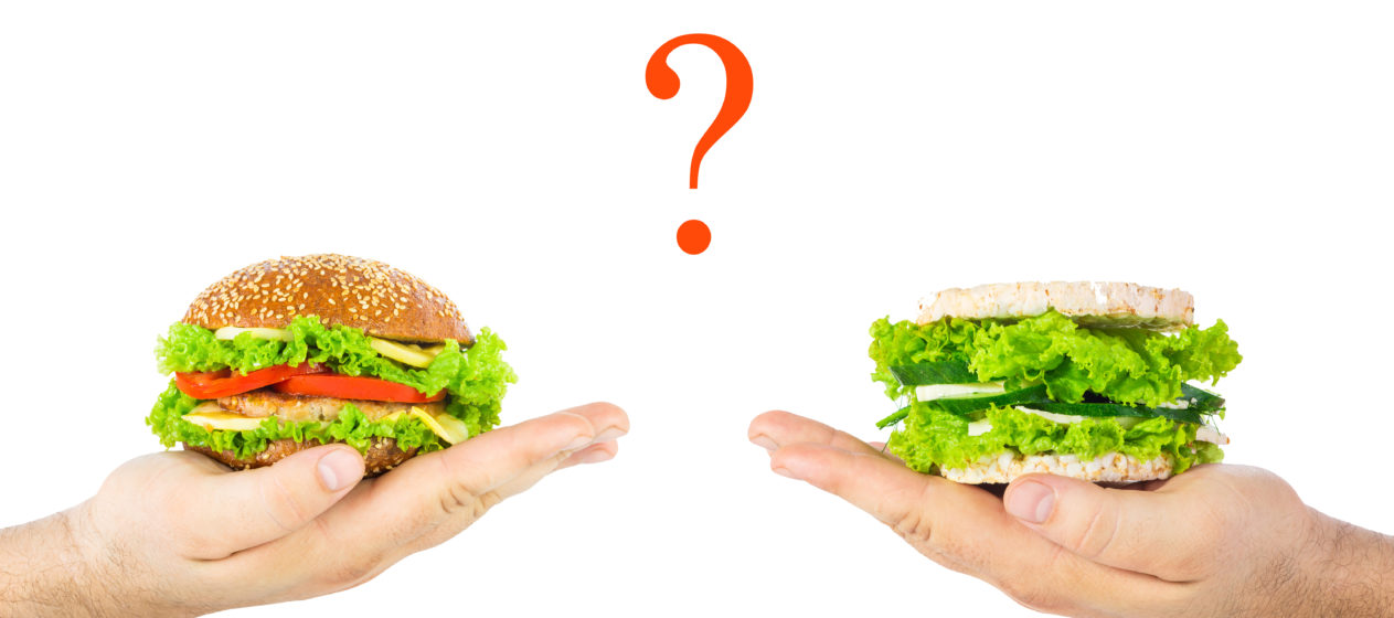 concept of choosing harmful junk food or natural health food. A man's hands holding classic burger and healthy burger with wholegrain cereal crispbreads vegetables herbs and cheese. Question mark.