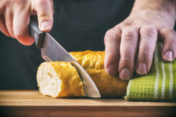 Man's hands cutting bread on wooden cutting board on dark background