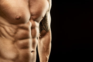 Men's muscular abdomen - close-up - on black background