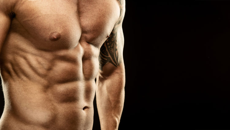 Men's muscular abdomen - close-up - on black background