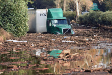 In this photo provided by the Santa Barbara County Fire Department, shows a semi-tractor trailer sits stuck in mud on U.S. Highway 101, in Montecito, Calif. on Tuesday, Jan. 9, 2018. Homes were swept away before dawn Tuesday when mud and debris roared into neighborhoods in Montecito from hillsides stripped of vegetation during a recent wildfire. (Mike Eliason/Santa Barbara County Fire Department via AP)